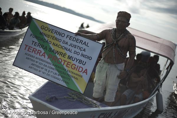 Un Munduruku brandit un panneau de démarcation sur le fleuve Tapajos