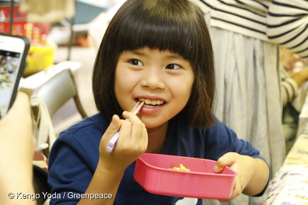 Petite Japonaise mangeant des légumes fraîchement cuisinés lors d'une foire sur l'agriculture écologique, Tokyo, août 2016.