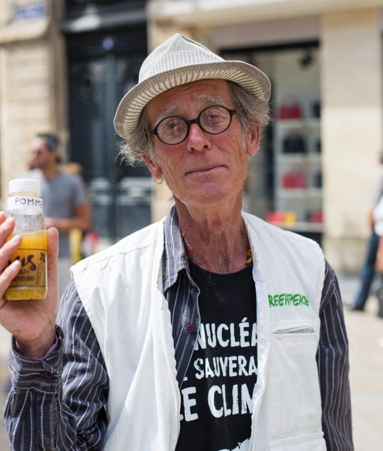 Jacques Delor montre une bouteille de jus de pesticides (campagne Greenpeace pour l'Agriculture écologique)