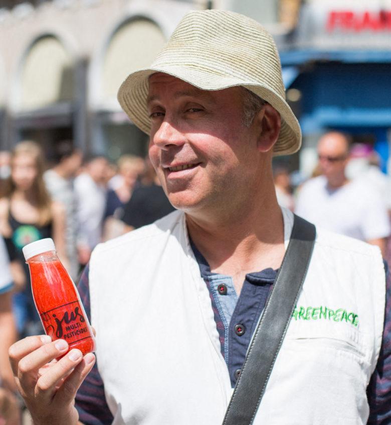 Michaël montre une bouteille de jus de pesticides (campagne Greenpeace pour l'Agriculture écologique)