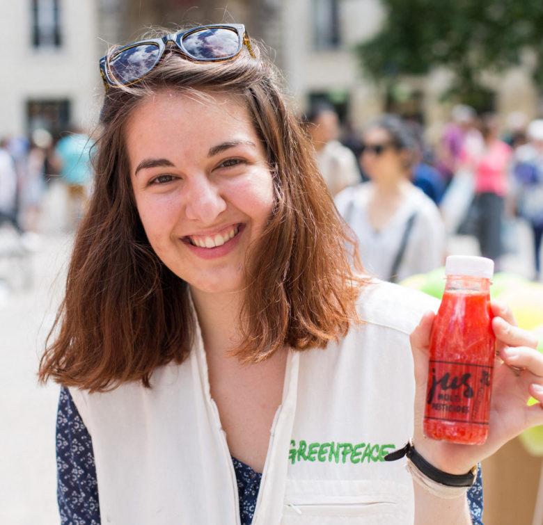 Paloma montre une bouteille de jus de pesticides (campagne Greenpeace pour l'Agriculture écologique)