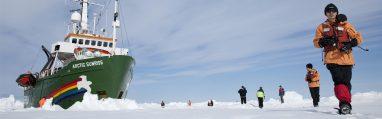 Des membres de l'équipage de l'Arctic Sunrise sur la glace, dans le passage Robeson, à proximité de leur bateau