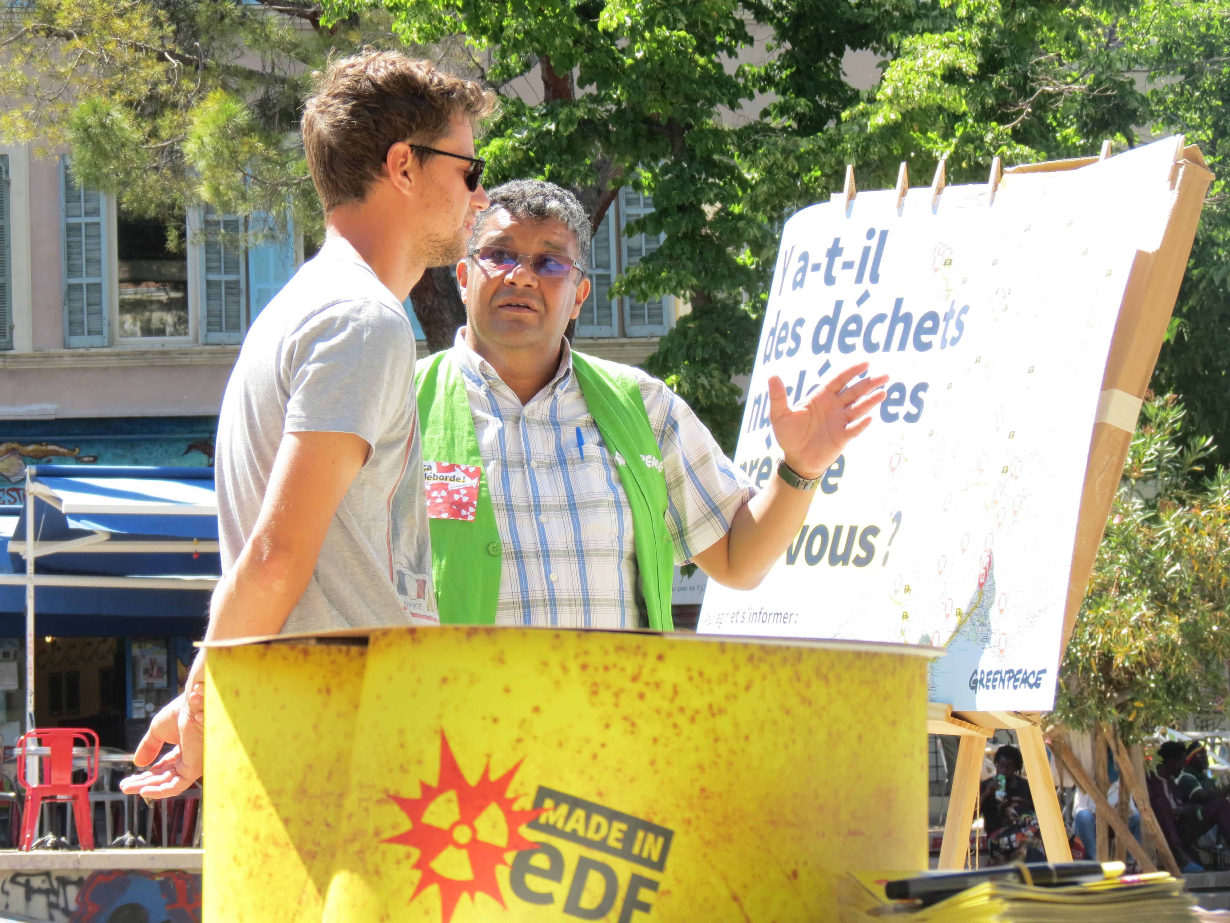 Militant Greenpeace parle des déchets nucléaires avec un passant