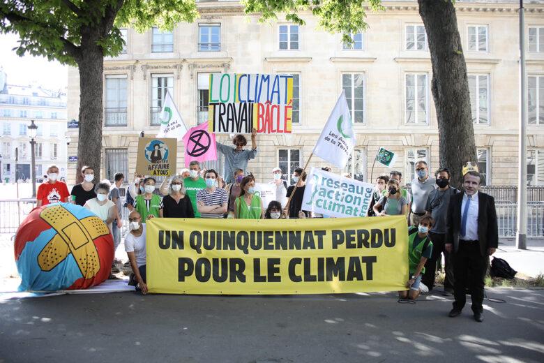 """Un groupe de militants et de militantes devant l'Assemblée Nationale, munis de drapeaux de leurs organisations, et d'une bannière où il est inscrit """"Un quinquennat perdu pour le climat"""""""